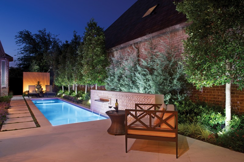 Small plunge pool with limestone decking features a tranquil waterfall spilling into the pool from a butterfly-tiled wall. A back-lit limestone wall creates a focal point amid lush plantings. -