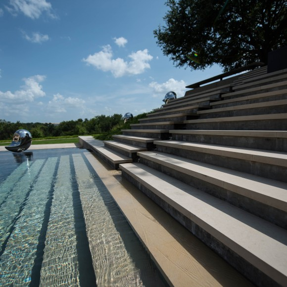 Limestone and concrete stairs leading into the pool at a Ft. Worth residence. Design by Hocker Design Group with installation by Bonick Landscaping.