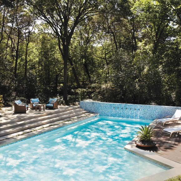 Irregular-shaped pool at Kessler Park residence features one-inch glass tile wall with round scuppers, architectural concrete seating area, and Ipe wood decking. Designed by Hocker Design Group with installation by Bonick Landscaping.