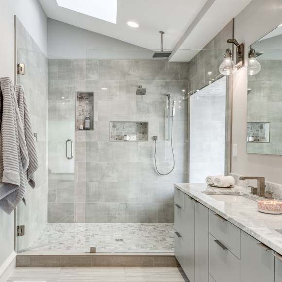 Arc award-winning project by Dallas Builders. ADA compliant bathroom remodel Modern gray bathroom with flat panel vanity, and industrial light fixtures