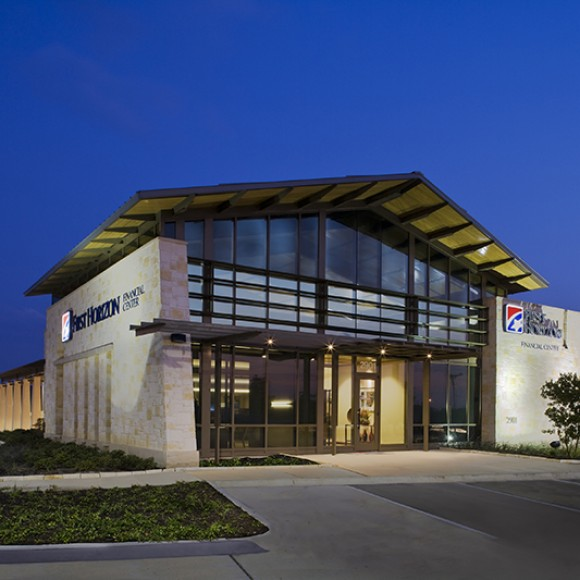 To establish a strong corporate image for expansion into the Dallas/Fort Worth market, the award-winning First Horizon prototype branch draws from regional architectural traditions and responds to evolving trends in consumer banking. Native limestone combines with clerestory windows and a dramatic roofline to offer a bold Texan expression and a welcoming retail-oriented presence in suburban settings. Interiors are flexible and respect the inherent demands of the changing technologies. Gary Zvonkovic Photography