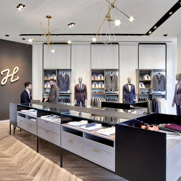 With a direct-to-consumer model, J. Hilburn, an online men's clothier, focuses on high quality Italian-made garments and custom experiences for each client. From recessed track lighting that conceal HVAC components to brass pulls and logo branded caps on fixtures, the design team helped to provide a tailored experience for clients while referencing the immaculate detailing of J.Hilburn's products and services throughout the space. Garrett Rowland