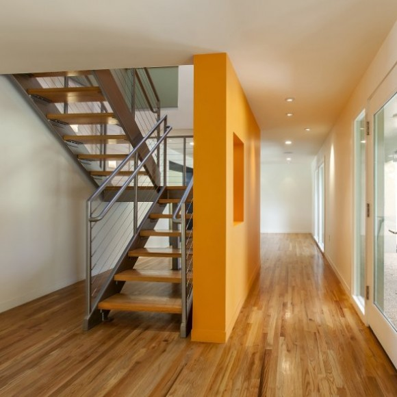 Under the Oak Tree: The existing entry and enclosure were outfitted with a new stair that floats in a light shaft that terminates with a series of operable skylights.  The two story orange wall creates a memorable entry experience as well as a dramatic connection between the first and second floors.